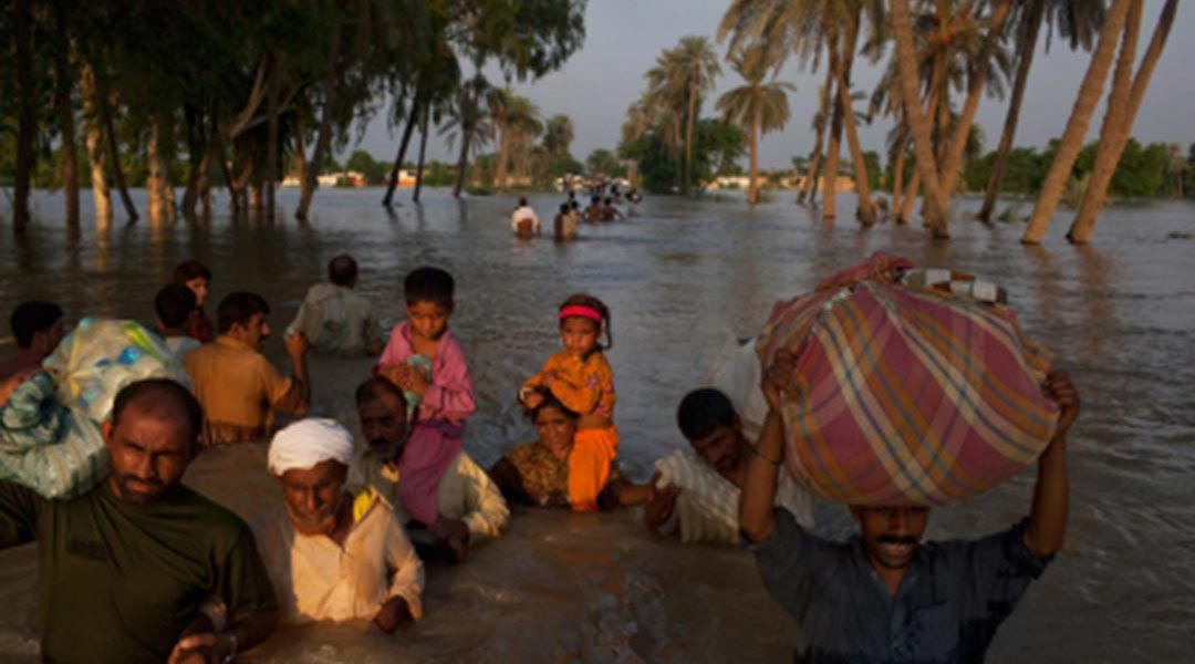 Villagers wade through flood waters after having evacuated their homes on August 10, 2010 in the village of Baseera near Muzaffargarh in Punjab, Pakistan
